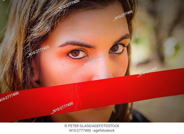 Young woman, outdoors, holding a red ribbon over her mouth