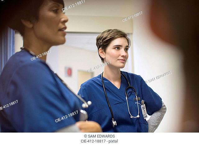 Two female doctors wearing navy blue scrubs, talking in hospital