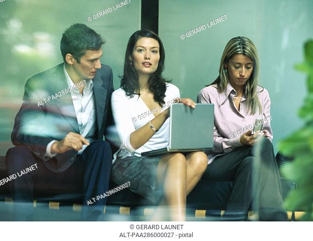 Businesswoman sitting between co-workers, looking up from laptop
