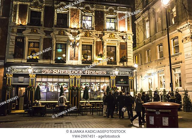 People having drinks in front of traditional Sherlock Holmes pub, Westminster, London, England, UK