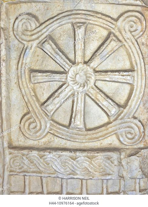 Ancient roman maritime design based on a ship's wheel and waves at sea, carved out of marble