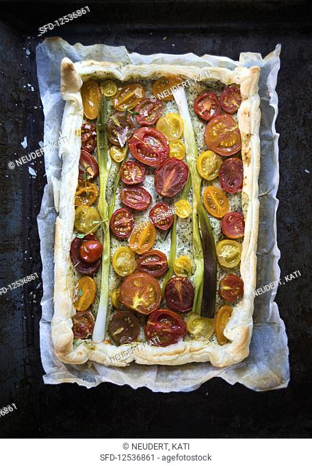 Vegan puff pastry quiche with herb sauce, tomatoes and spring onions