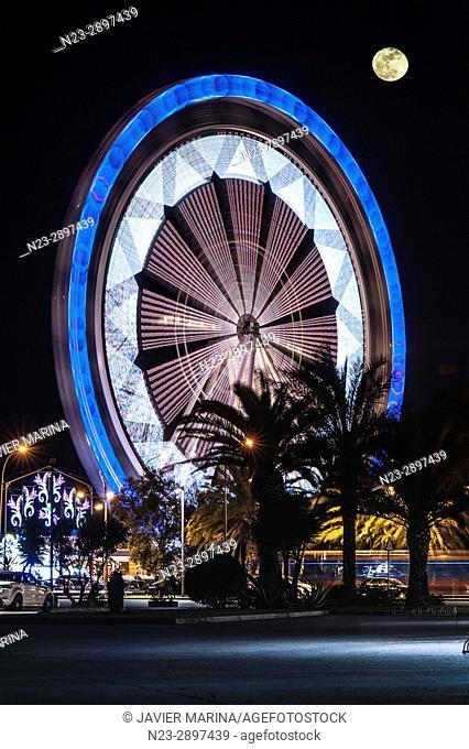 Ferris wheel and moon at the fair in Valencia, Valencian Community, Spain