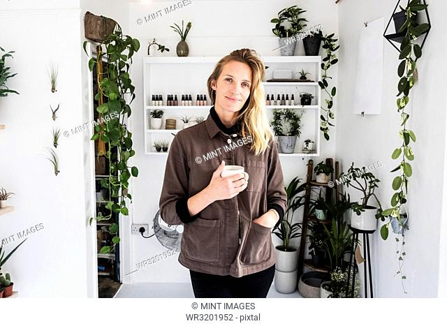 Female owner of plant shop smiling at camera, a selection of plants on wooden shelves