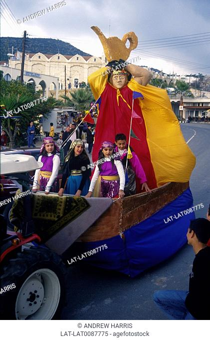 Arrival of the King carnival parade. Huge figure of king on float. Teapot shape on head. Children in costume