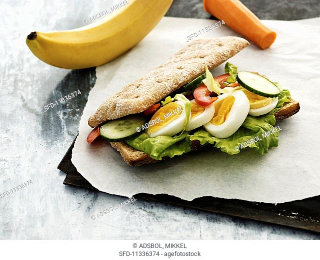 A sandwich with hard boiled eggs, tomatoes and cucumber