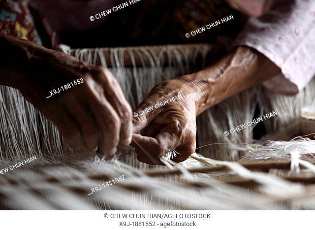 Close-up of Weaver weaving in a weaving mill, Inle Lake, Shan state, Myanmar, Burma