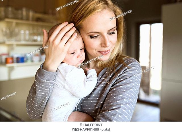 Smiling mother holding baby at home