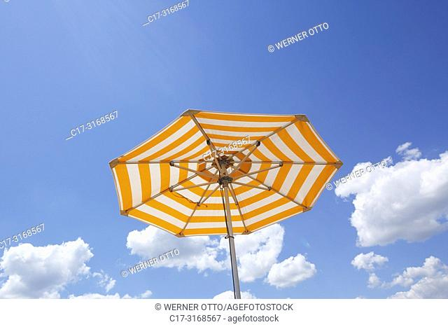 one parasol on a cruise ship against the blue sky, yellow and white, cumulus clouds, holiday, freetime, recreation, relaxation, sunlight, sunshine