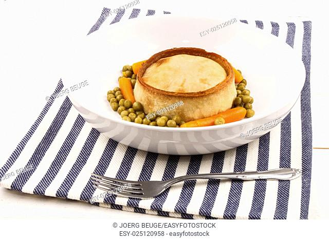 baked scotch pie with carrot and pea in a white deep plate