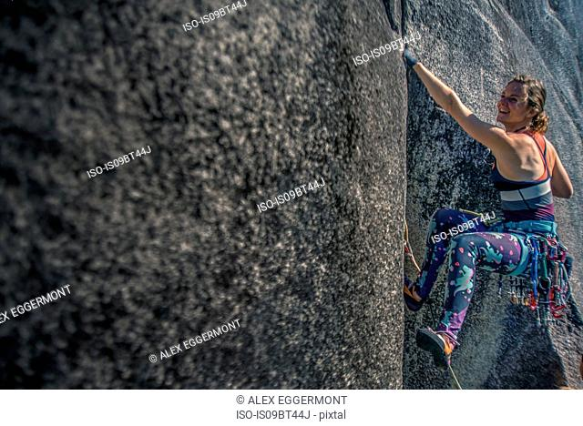 Young female climber climbing rock face, Smoke Bluffs, Squamish, British Columbia, Canada