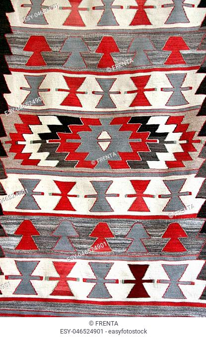 Texture of georgian traditional wool carpet with geometric pattern of red, gray and white colors, Georgia