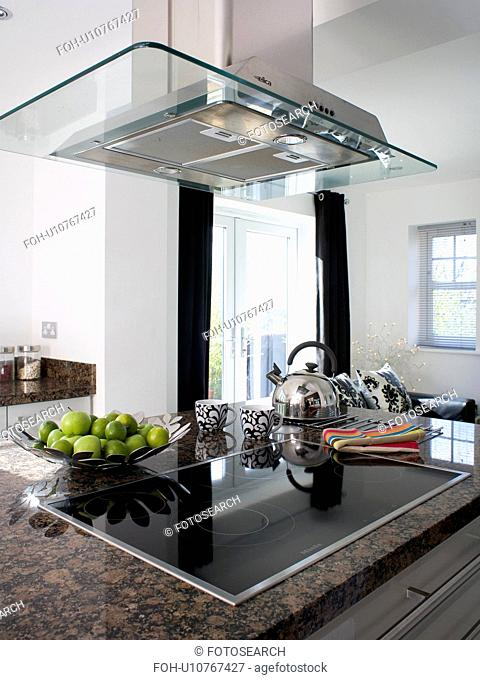 Large glass and steel extractor above halogen hob in modern kitchen