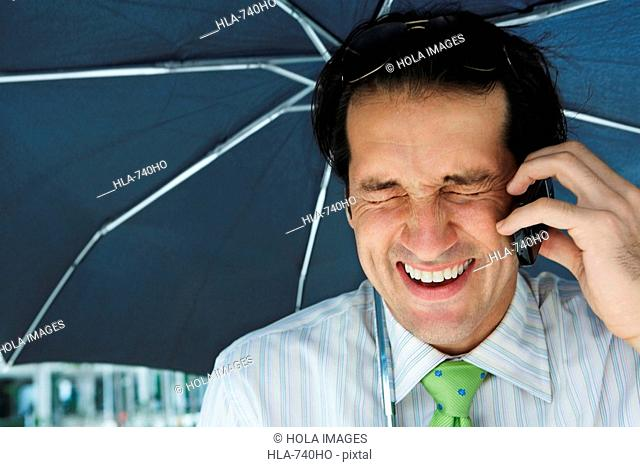 Close-up of a businessman using a mobile phone under an umbrella