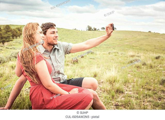 Young couple sitting on hilltop taking smartphone selfie, Cody, Wyoming, USA