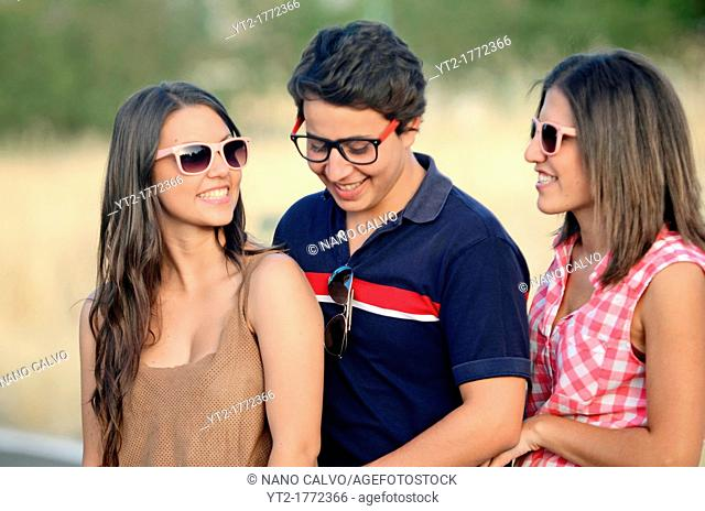 Two young women and a young man have fun outdoors