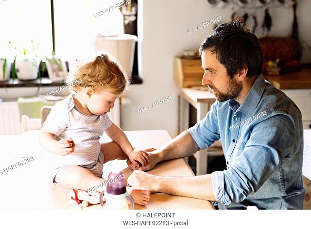 Father playing with little boy sitting on kitchen table