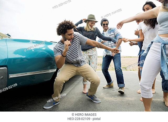 Friends dancing outside convertible at beach