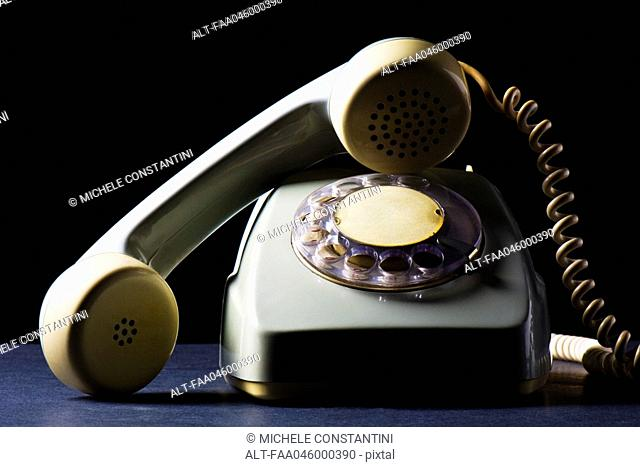 Rotary telephone with receiver off the hook, still life