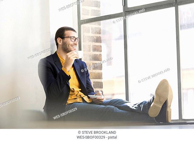 Businessman sitting on window sill, drinking coffee