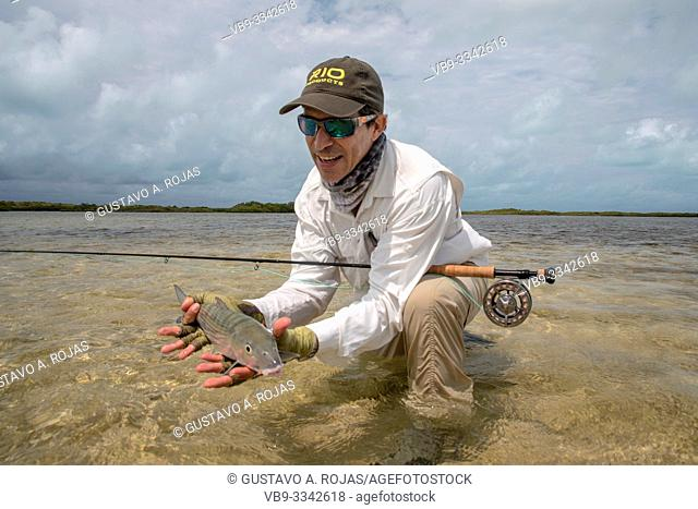 A fly fisherman holding bonefish on the beach . los roques Venezuela