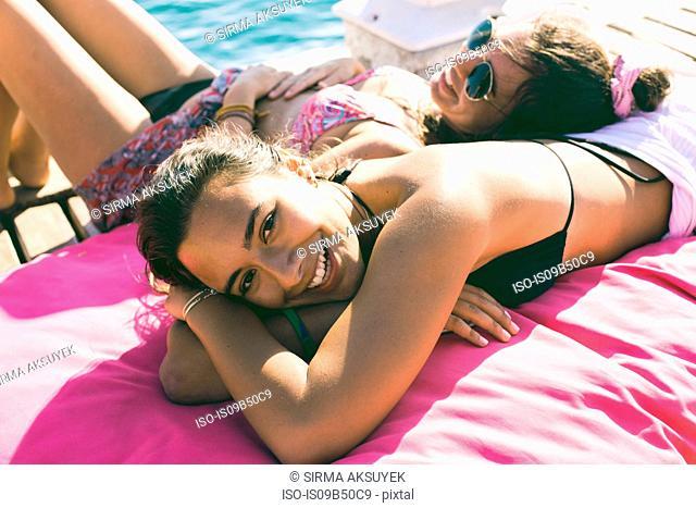 Portrait of young woman and best friend sunbathing on pier at Burgaz Island, Istanbul, Turkey