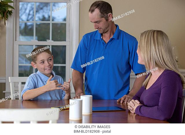 Caucasian family signing at dinner table