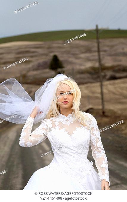 A young bride outdoors wearing her wedding dress