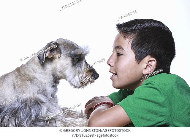 A boy and a Miniature Schnauzer share some bonding time together in this studio photo