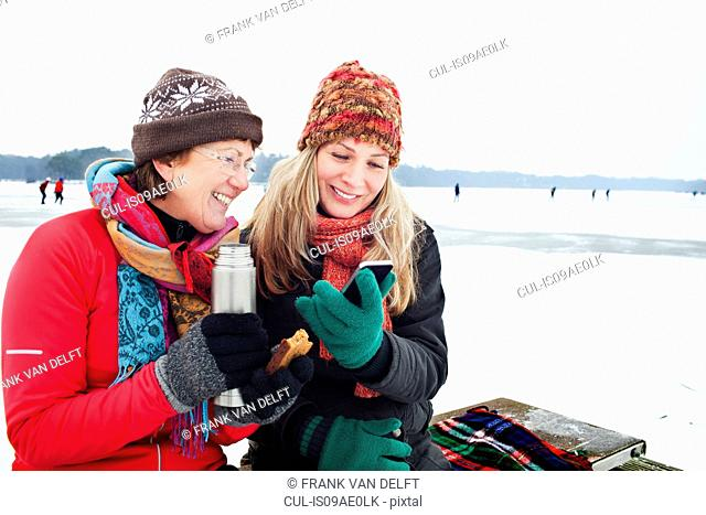 Women having hot drinking and looking at smartphone