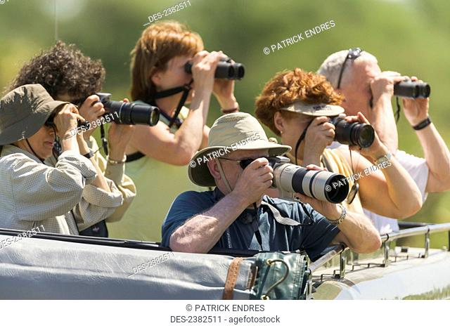 Tourists photograph and watch wildlife from a land cruiser in the Serengeti National Park; Tanzania