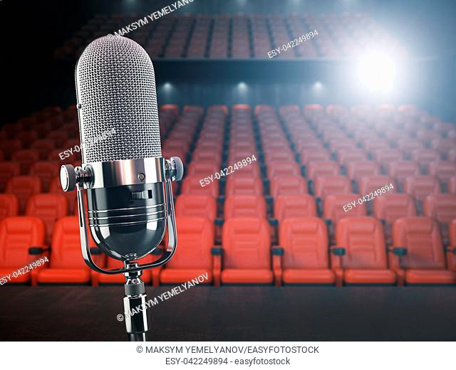 Vintage microphone on the stage of concert hall or theater with red seats and spot light. 3d illustration