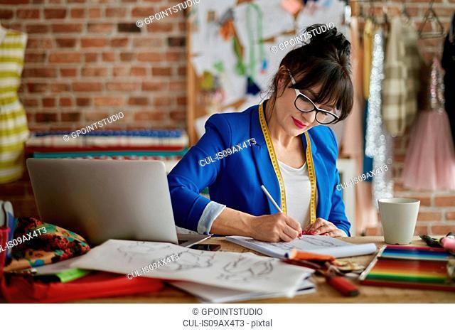 Woman in design studio sitting at desk sketching fashion design