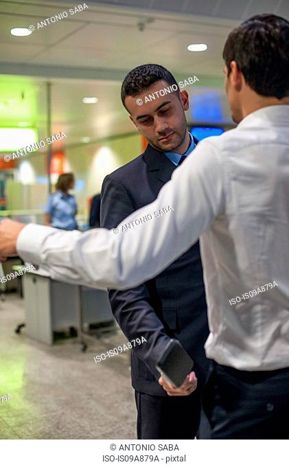 Security guard checking male passenger in airport security