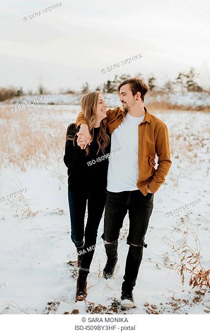 Happy couple enjoying walk in snowy field