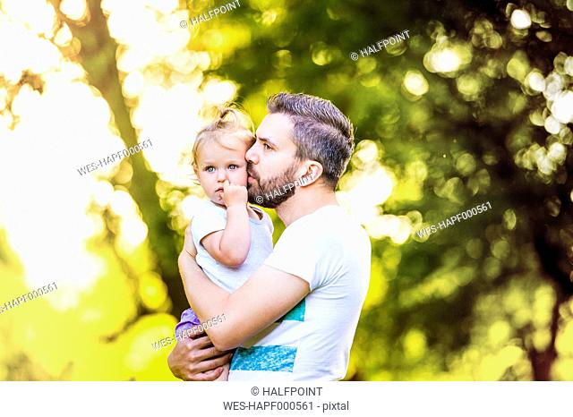 Father holding his little daughter on his arms