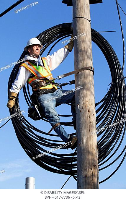 Cable lineman preparing to install new cable from power pole