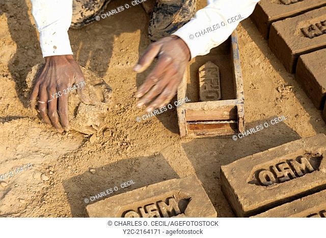 Rajasthan, India. Man Producing Bricks from Mud Formed by Brick Mold. Note the Hindu Swastika on the Company Logo