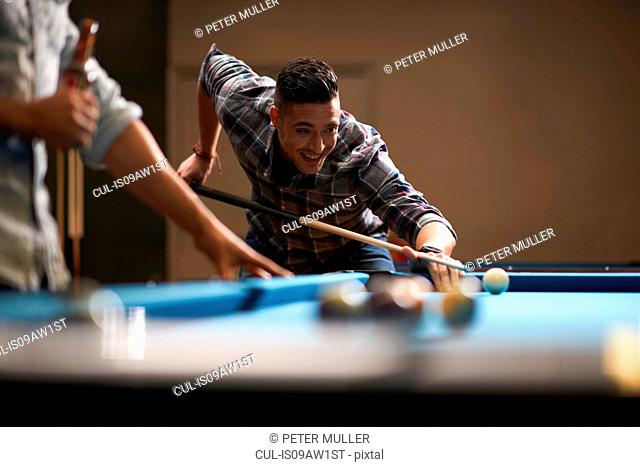 Man playing pool, friend with beer in foreground