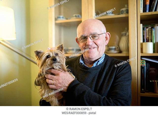 Portrait of senior man with his Yorkshire terrier at home