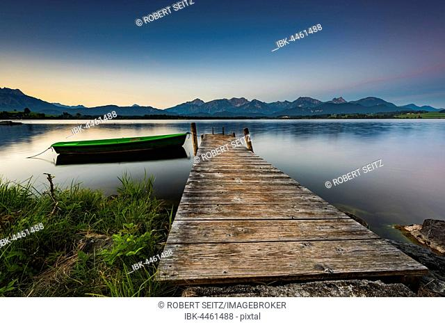 Rowing boat at dock with mountain lake, Allgäu Alps at back, blue hour, Hopfensee, Hopfen am See, Ostallgäu, Bavaria, Germany