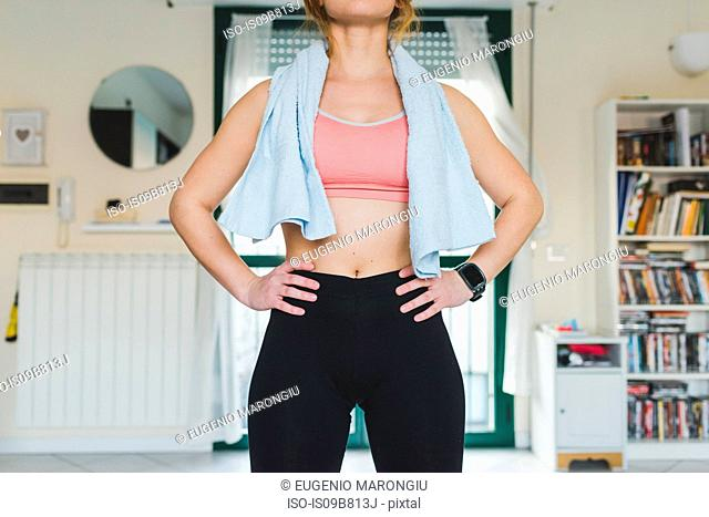 Mid section of young woman training, standing with hands on hips