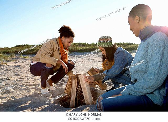 Three friends on beach, preparing camp fire