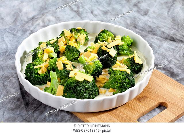 Broccoli garnished with cheese in plate on chopping board, close up