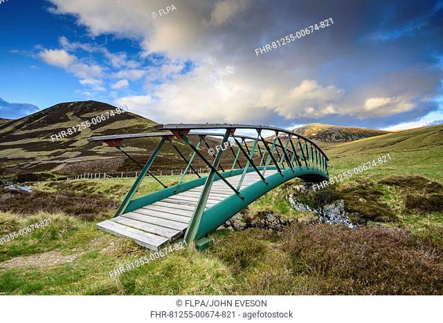 Metal footbridge over river in glen, in evening sunlight, Clunie Water, near Braemar, Cairngorms N.P., Aberdeenshire, Highlands, Scotland, May
