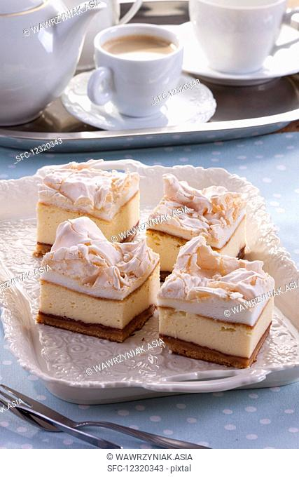 Four pieces of cheesecake topped with meringue, served with coffee