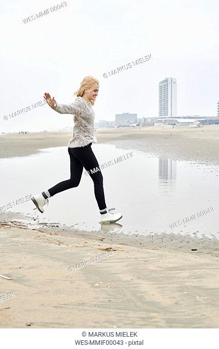 Netherlands, Zandvoort, happy young woman having fun on the beach