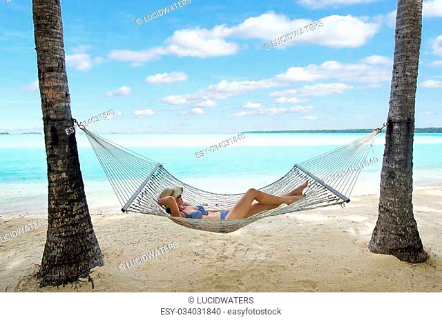 Happy woman relaxing on hammock on the beach during travel vacation on tropical island in Aitutaki lagoon, Cook Islands