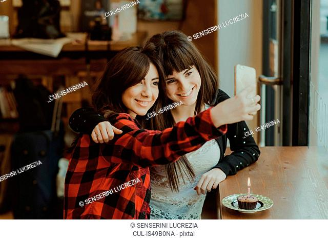 Two female friends, sitting in cafe, taking selfie, using smartphone, cupcake with candle on counter