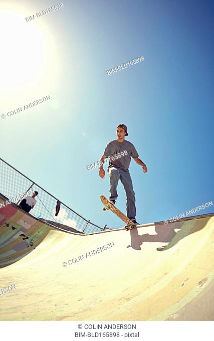 Man watching friend performing trick at skate park